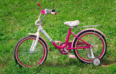 The bicycle for the girl on a green lawn. — Stock Photo