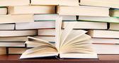 Högen med böcker och öppnade boken — Stockfoto