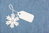 Blank paper label tag and snowflake on blue jeans — Foto Stock