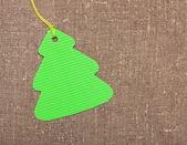 Christmas tree shape label tag on sackcloth — Stock Photo