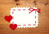 Blank Valentines card with felt hearts on wooden background — Stock Photo