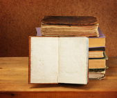 Books stack and opened book on wooden table. Dark background. — Stock Photo