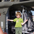 McGUIRE AIR FORE BASE-WRIGHTSTOWN, NEW JERSEY, USA-MAY 12: A young boy is all smiles as he prepares to step out of a U.S. Army helicopter after touring it during the base's Open House on May 12, 2012. - Stock fotografie