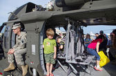 McGUIRE AIR FORE BASE-WRIGHTSTOWN, NEW JERSEY, USA-MAY 12: Children of all ages are seen touring a U.S. Army helicopter on static display during the base's Open House held on May 12, 2012. — Stock Photo