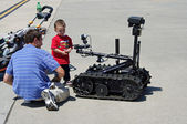 McGUIRE AIR FORE BASE-WRIGHTSTOWN, NEW JERSEY, USA-MAY 12: A young boy is seen inspecting a remote controlled robot during the base's Open House held on May 12, 2012. — Stock Photo