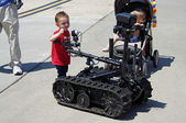 McGUIRE AIR FORE BASE-WRIGHTSTOWN, NEW JERSEY, USA-MAY 12: A young boy is fascinated with a remote controlled robot as seen in this photograph taken during the base's Open House held on May 12, 2012. — Stock Photo