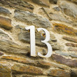Stock Photo: Thirteen on stone wall
