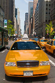 Manhattan buildings and taxis driving on a sunny day, New York City, USA — Foto de Stock