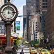 New York urban city life with taxis passing by 5th avenue and a big street clock. — Stock Photo