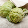Three artichokes on a dishcloth — Stock Photo