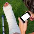 Leg in plaster and blank screen smart phone - Stock Photo