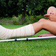 Girl with leg in plaster chatting with her smartphone - Stock Photo