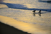 Surfers at sunset — Stock Photo