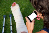 Leg in plaster and blank screen smart phone — Stockfoto