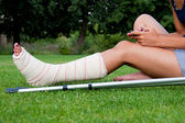 Girl with leg in plaster chatting with her smartphone — Stock Photo