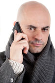 Man with coat and scarf on the phone. — Stock Photo