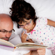 Father and daughter reading a book in bed - Stock Photo
