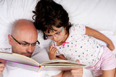 Father and daughter reading a book in bed — Stock Photo