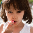 Royalty-Free Stock Photo: Little girl putting on lipstick