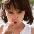 Little girl putting on lipstick — Stock Photo