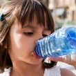 Thirsty little girl drinking water — Stock Photo