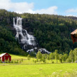 Farm next to a waterfall in Norway — Stock Photo