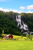 Red farm next to a waterfall. — Stock Photo