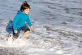 Happy child caught by waves — Stock Photo