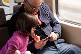 Father and daughter on train with smart phone — Foto Stock