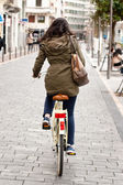 Woman cycling down the street — Stock Photo