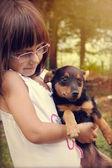 Happy little girl holding her dog — Stock Photo