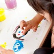 Little girl painting faces with fingers — Stock Photo