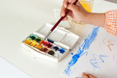 Hand of child with paintbrush on watercolor set — Stock Photo