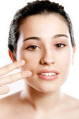 Beautiful woman applying foundation on face with fingers — Stock Photo