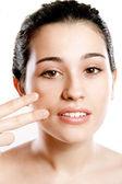 Bella donna applicando la fondazione sul viso con le dita — Foto Stock