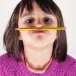 Little girl holding a pencil like a mustache.  — Stock Photo