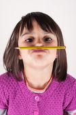 口ひげのような鉛筆を保持している小さな女の子. — ストック写真