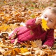 Baby discovering autumn leaves — 图库照片