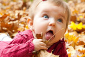 Cute baby girl eating autumn leaves — Stock Photo