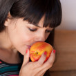 Young woman smelling a nectarine — Stock Photo