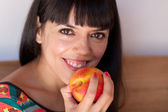 Cute woman with a nectarine — Stock Photo