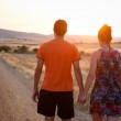 Young couple walking at sunset — Stock Photo #31487317