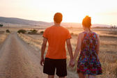 Young couple walking at sunset — Stock Photo