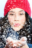 Christmas girl blowing snow in hands — Stock Photo