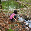 Little girl playing with water in a river  — Stock Photo