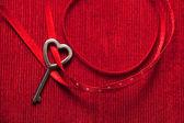 Heart shaped key on red velvet — Stockfoto