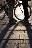 Legs of a young couple face to face with bicycle — Stock Photo
