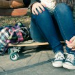 Stock Photo: Legs of a girl sitting on a skateboard