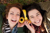 Happy teen girls sharing music — Stock Photo