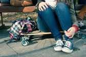 Legs of a girl sitting on a skateboard — Stock Photo